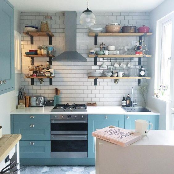 une petite cuisine bleue avec un dosseret de carreaux blancs et des comptoirs blancs ainsi que des étagères en bois