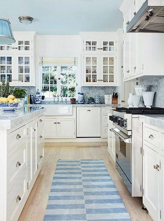 une cuisine traditionnelle neutre avec des comptoirs bleus et un dosseret, des tapis et des lampes pour une touche de couleur