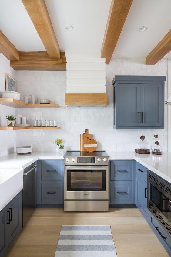 une cuisine bleu ardoise avec un dosseret de carreaux blancs et des comptoirs ainsi que des touches de bois pour la chaleur
