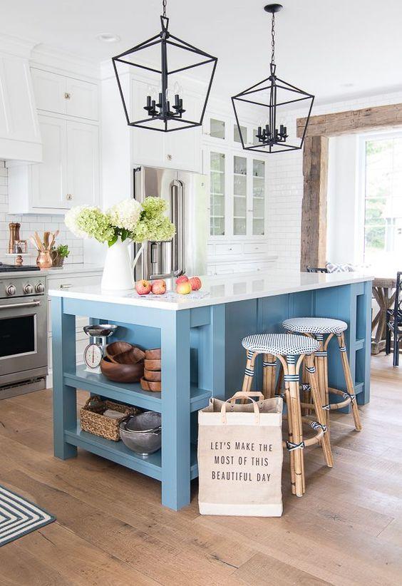 une cuisine côtière traditionnelle avec des armoires blanches, un îlot de cuisine bleu avec un comptoir blanc et des tabourets en rotin bleus