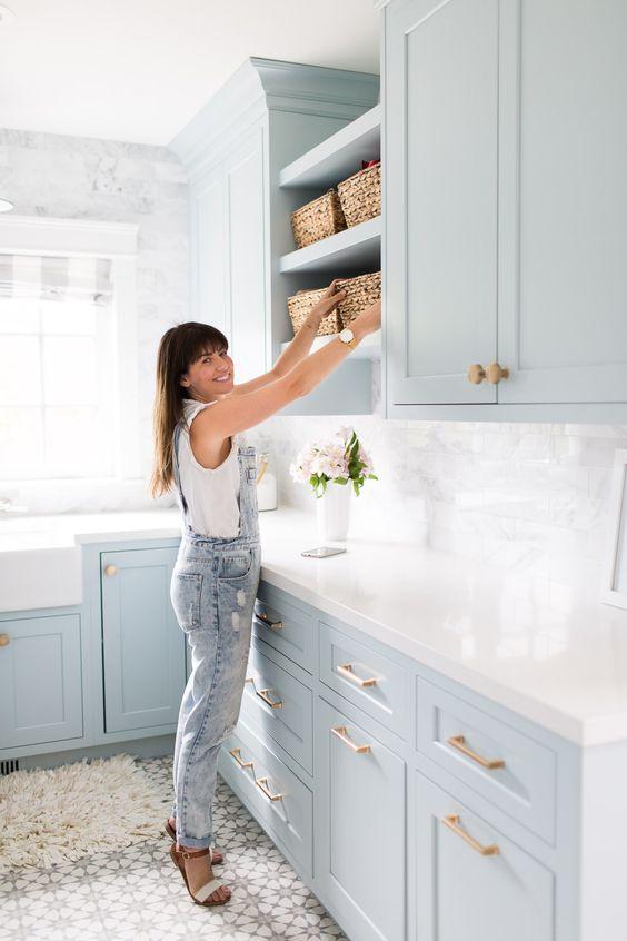 une cuisine bleu poudre douce avec un dosseret et des comptoirs blancs ainsi que des touches de bois naturel