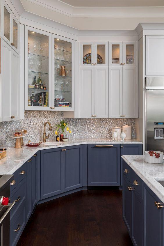 une cuisine traditionnelle avec des armoires inférieures bleues, des armoires supérieures neutres, un bacskplash en nacre et des touches d'or