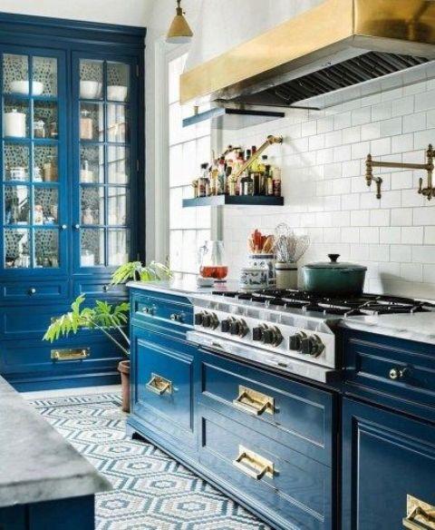 une cuisine bleue super brillante avec un dosseret de carreaux blancs et beaucoup d'or pour obtenir un style art déco