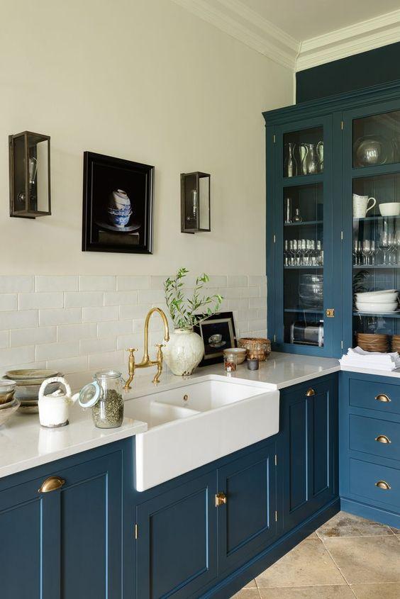 une cuisine turquoise rafraîchie avec un dosseret et un comptoir de carreaux blancs ainsi que des poignées et des accessoires dorés