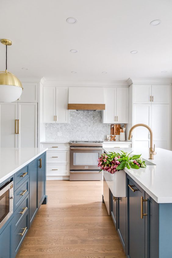 une cuisine élégante avec des îlots de cuisine bleus, des armoires et des comptoirs blancs ainsi que des touches de laiton chics