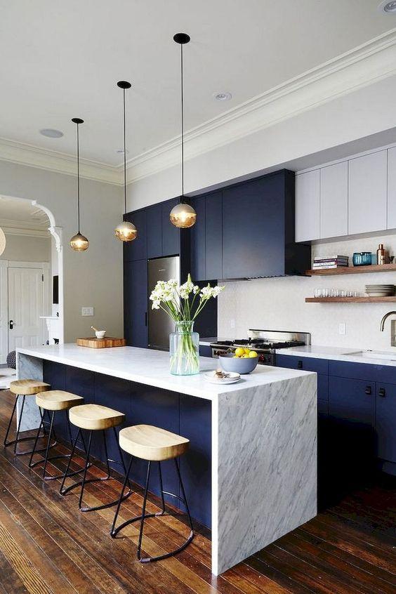 une cuisine contemporaine inspirante avec des armoires bleu marine et blanches, des comptoirs en pierre blanche, des tabourets en bois et des suspensions