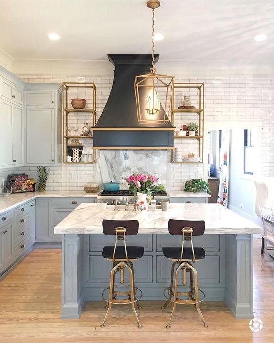 une cuisine art déco avec des armoires bleu poudre et un îlot de cuisine complété d'un comptoir en pierre blanche et d'un dosseret de carreaux