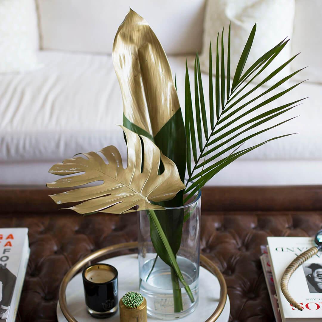 Trempez le feuillage tropical dans la peinture dorée