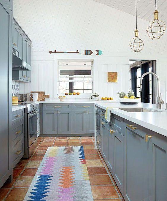 une cuisine lumineuse avec des armoires grises, des murs et des comptoirs blancs et des touches d'or ici et là