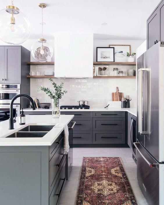 une cuisine contemporaine avec des armoires grises, une hotte blanche et un dosseret de carreaux et des comptoirs blancs plus un tapis boho
