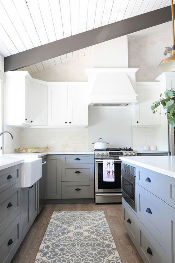 une cuisine chic à deux tons avec des armoires supérieures blanches et des armoires inférieures gris clair, des poignées noires et des poutres en bois sombres