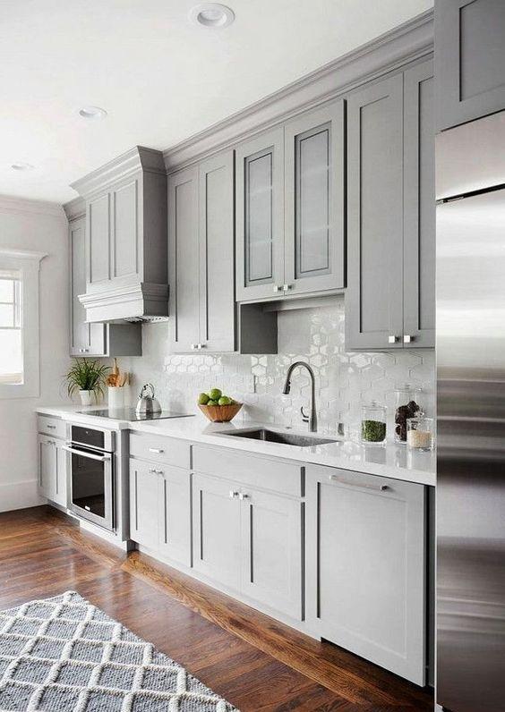 une cuisine chic et contemporaine gris tourterelle avec un dosseret de carreaux blancs et des comptoirs ainsi qu'un riche sol teinté