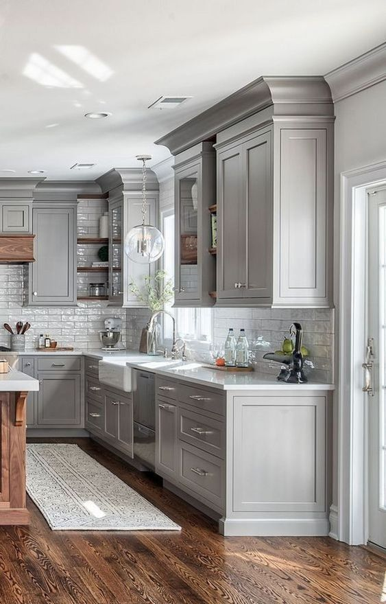 une cuisine de ferme en gris tourterelle avec un dosseret de carreaux blancs, une lampe à bulles et du bois teinté riche pour une touche chaleureuse