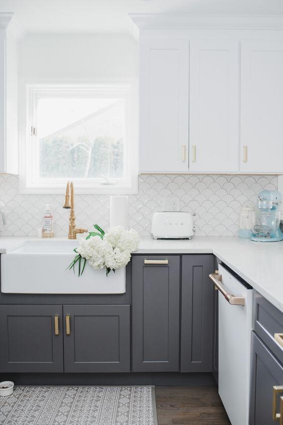 une cuisine contemporaine avec des armoires supérieures blanches et grises inférieures, des poignées en or et en laiton et un dosseret en écailles de poisson blanc