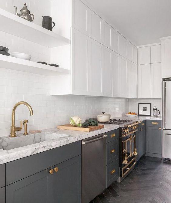 une cuisine contemporaine avec des armoires inférieures grises, des armoires supérieures blanches, des touches d'or et de laiton, des comptoirs blancs