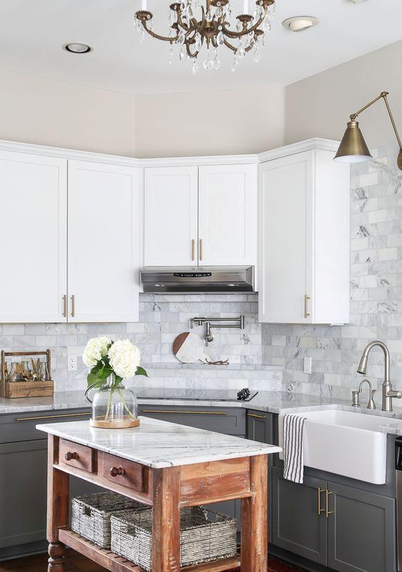 une cuisine de ferme avec des armoires supérieures blanches, des gris graphite, un dosseret de carreaux de marbre et un îlot de cuisine teinté