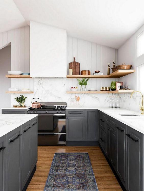 une magnifique cuisine contrastée avec des armoires gris graphite, des comptoirs blancs et un dosseret, une hotte, des étagères en bois pour un look plus doux