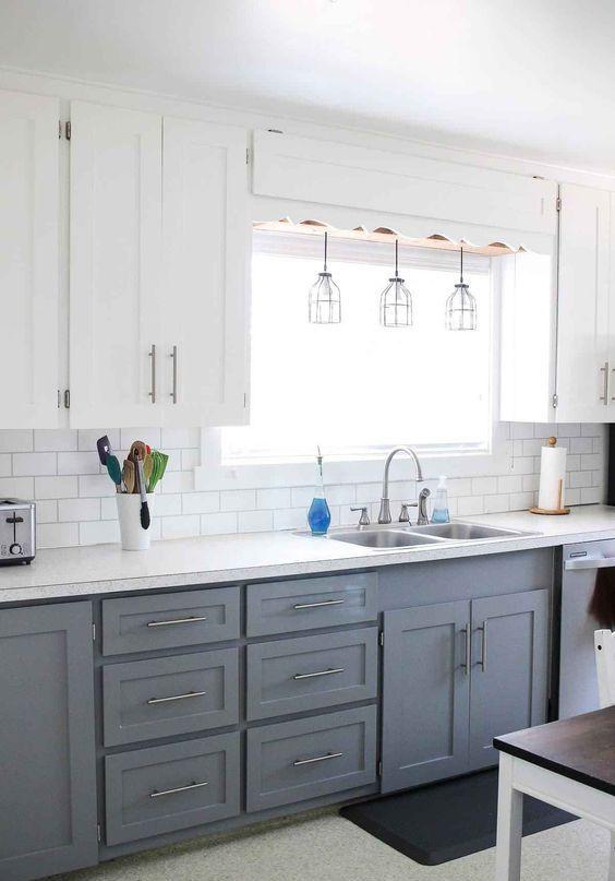une cuisine de ferme moderne avec des armoires supérieures blanches, des grises inférieures, des suspensions et des touches métalliques ici et là