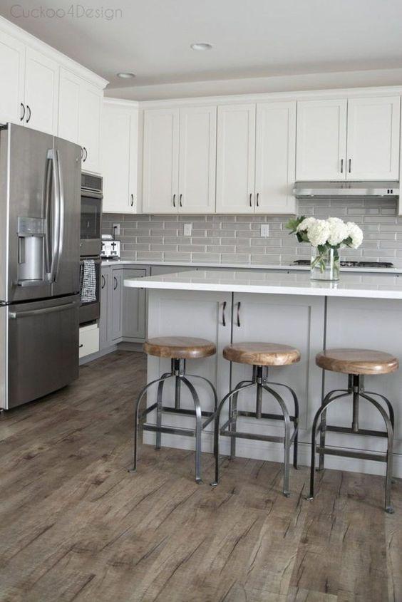 une cuisine moderne du milieu du siècle avec des armoires inférieures gris tourterelle, des armoires supérieures blanches, un dosseret de carreaux gris et un îlot de cuisine gris