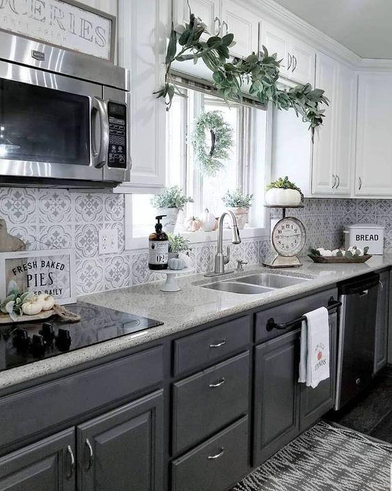 une cuisine élégante avec des armoires supérieures blanches, des armoires inférieures gris graphite, un dosseret de carreaux de mosaïque et des comptoirs en pierre