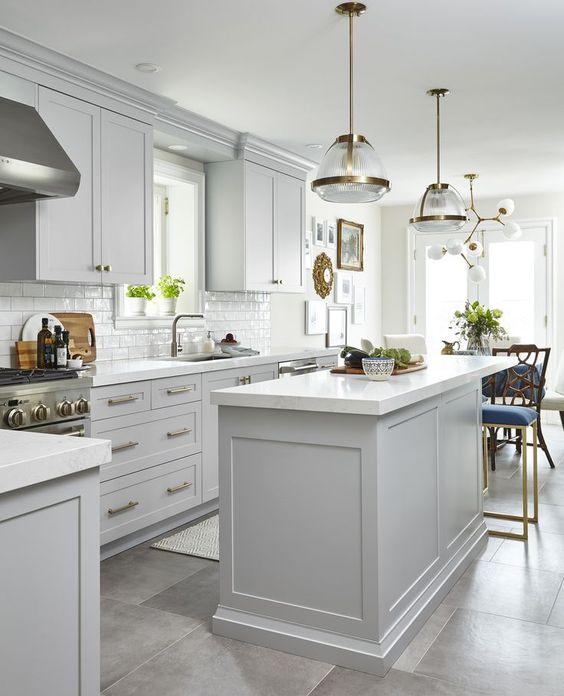 une cuisine moderne du milieu du siècle avec des armoires gris tourterelle, des touches dorées et des lampes et des lustres chics pour une sensation élégante