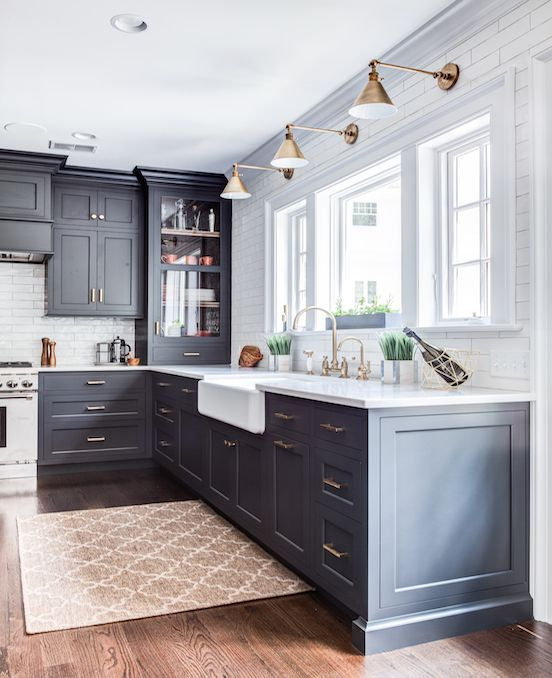 une cuisine moderne du milieu du siècle avec des armoires gris graphite, des comptoirs blancs, des lampes et des poignées en laiton ainsi que des carreaux blancs sur le dosseret