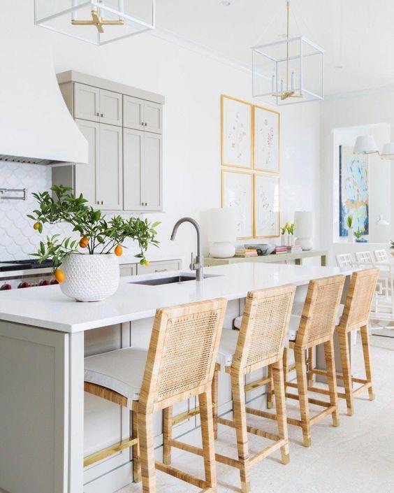 une cuisine aérée avec des armoires gris tourterelle et un îlot de cuisine, des comptoirs en pierre blanche, des tabourets en osier et des lustres à cadre