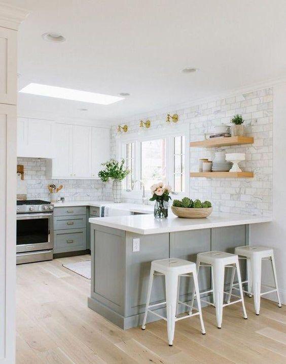 une cuisine éthérée avec des armoires inférieures gris tourterelle, des armoires supérieures blanches, des comptoirs blancs et des murs en carrelage plus des touches d'or