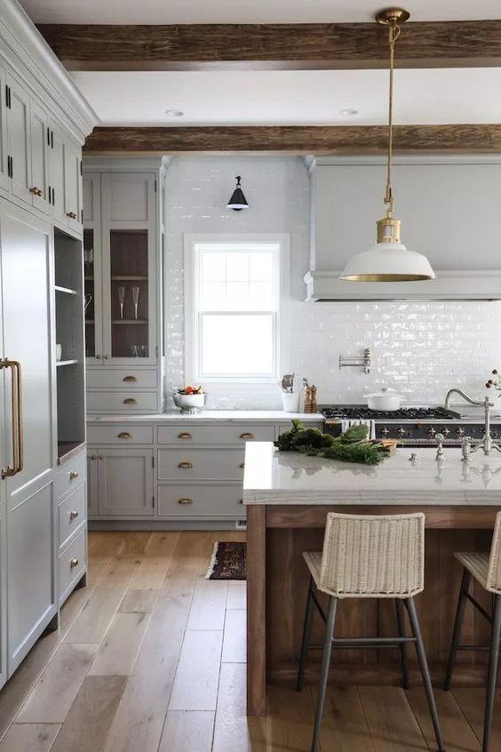 une cuisine vintage avec des armoires gris tourterelle, un dosseret de carreaux blancs, des lampes blanches et des poutres en bois plus un îlot de cuisine