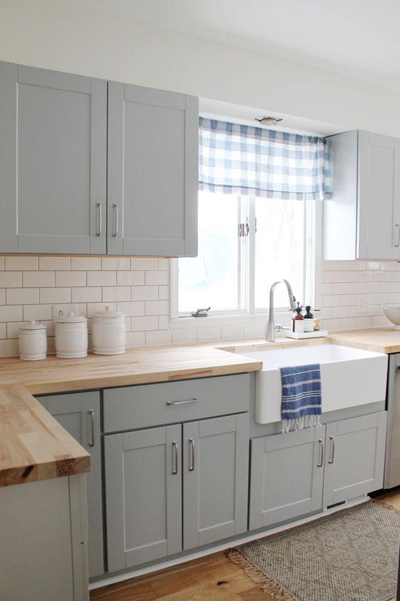 une cuisine aérée avec des armoires gris tourterelle, un dosseret de carreaux de métro blanc et des cuntertops en bois a l'air cool et audacieux