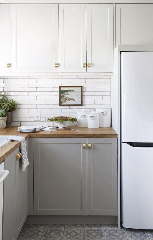 une cuisine bicolore avec des armoires supérieures blanches, des armoires inférieures gris tourterelle, des comptoirs en bois et des poignées dorées