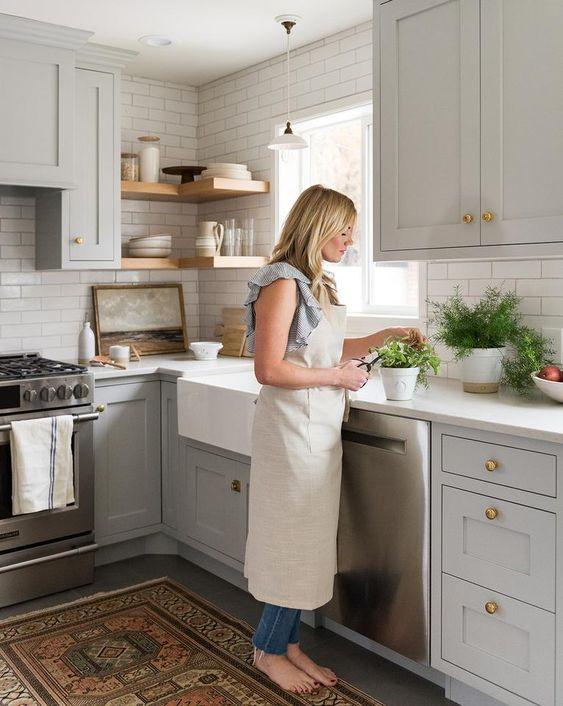 des armoires gris tourterelle, un dosseret de carreaux blancs et des comptoirs blancs, des étagères en bois et un tapis boho pour un look chic