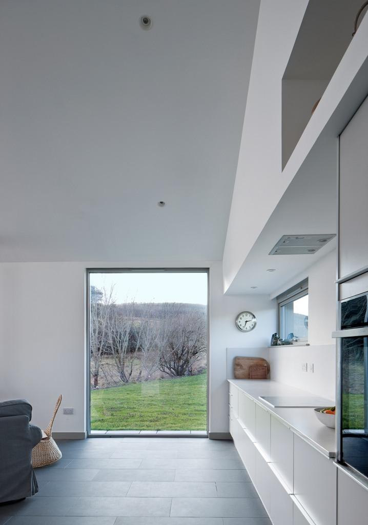 La cuisine est faite avec des armoires blanches élégantes, il y a une grande fenêtre et un dosseret de fenêtre