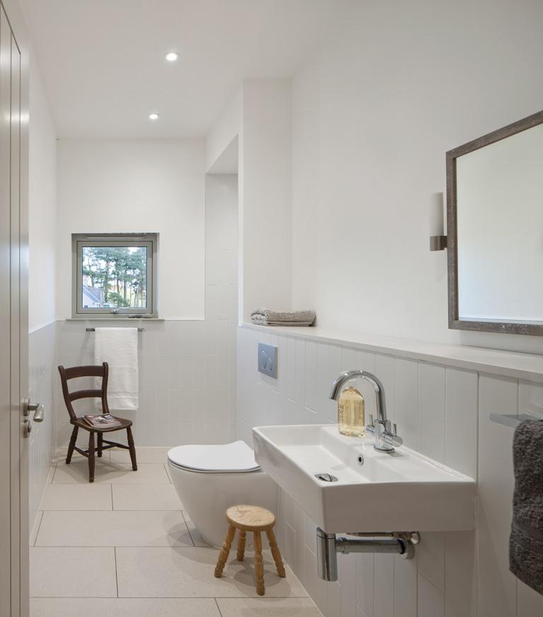 La salle de bain est neutre, avec des tules blanches de différentes tailles et une fenêtre pour plus de lumière