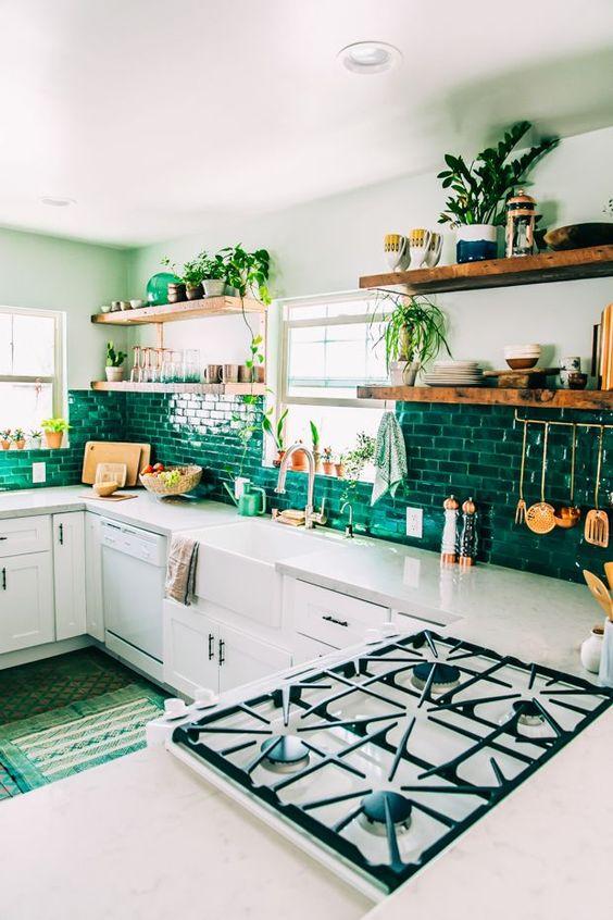 une cuisine bohème avec des armoires blanches, un dosseret de carreaux vert clair, beaucoup de verdure et des tapis verts
