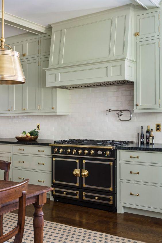 une cuisine art déco lumineuse en vert pâle, avec un dosseret de carreaux blancs, une cuisinière vintage et des touches dorées