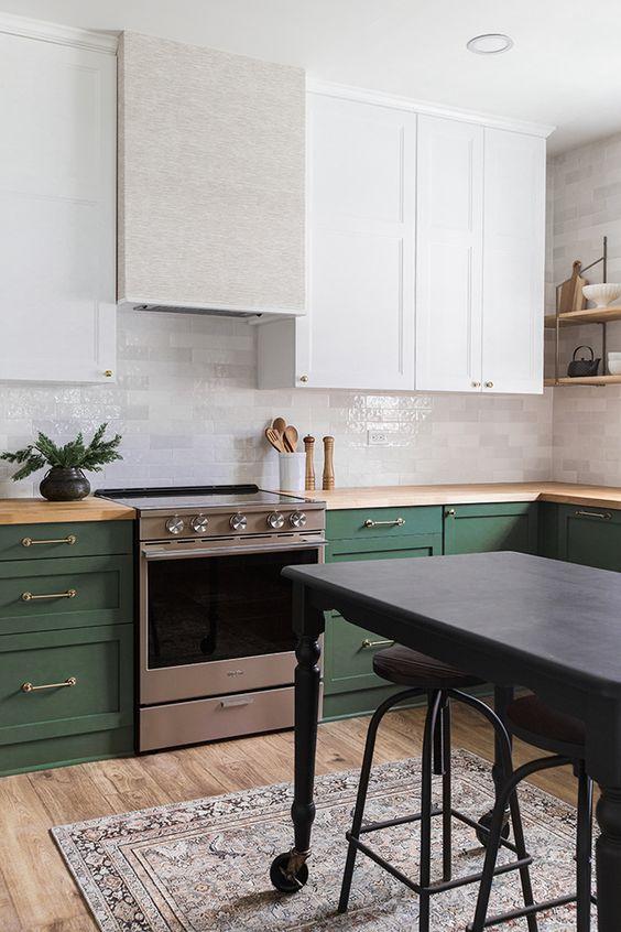 une cuisine chic et audacieuse avec des armoires blanches et vertes, des touches métalliques, des comptoirs en bois et un îlot de cuisine gris foncé