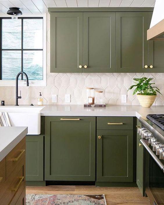 une cuisine verte accrocheuse avec un dosseret de carreaux blancs et des touches dorées ainsi que des luminaires noirs est super élégante