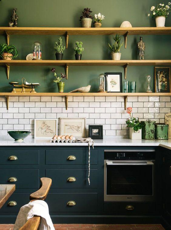 une cuisine moderne accrocheuse avec des murs verts, des carreaux de métro blancs et des armoires sarcelle diluées avec des étagères en bois