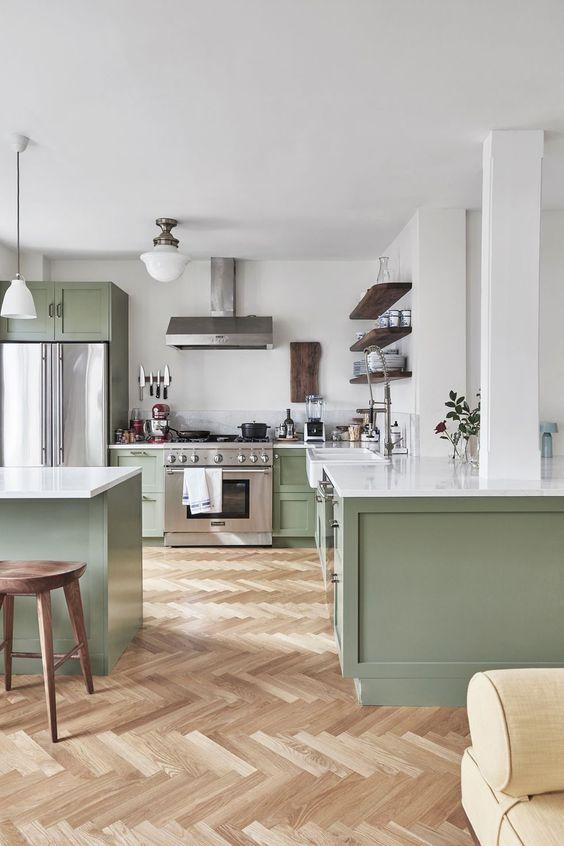 une cuisine contemporaine chic en vert clair et blanc, avec des touches de bois foncé et des comptoirs blancs est très accueillante