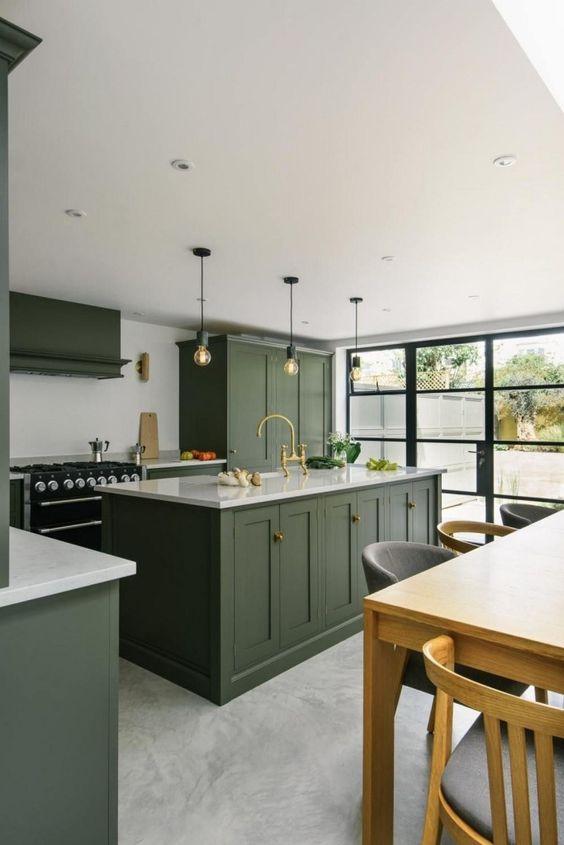 une cuisine contemporaine chic avec des armoires vertes, des comptoirs blancs, une cuisinière noire et des ampoules sur l'îlot de cuisine