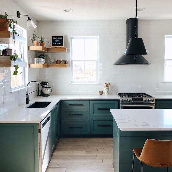 une cuisine contemporaine avec des armoires vertes, des murs de carreaux blancs, des comptoirs en pierre blanche et des luminaires et lampes noirs