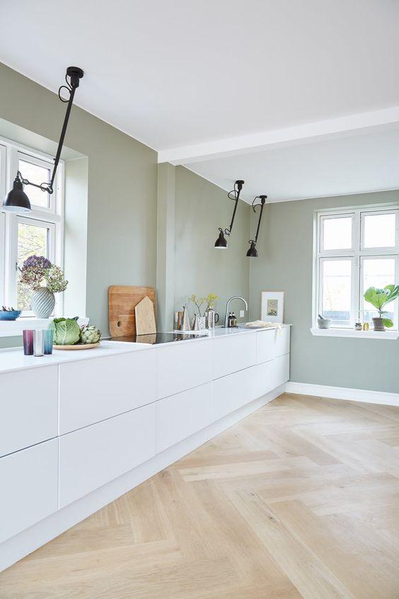 une cuisine minimaliste avec des murs vert pâle, des armoires blanches et élégantes, des plafonniers noirs semblent frais et naturels