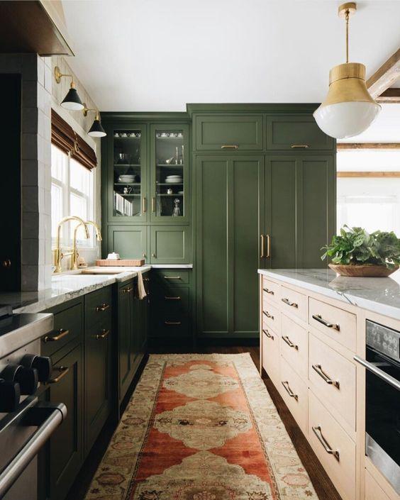 une cuisine vert foncé, un îlot de cuisine en bois clair, des comptoirs en pierre blanche et des touches dorées pour une sensation moderne du milieu du siècle