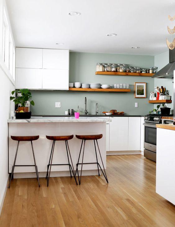 une cuisine minimaliste avec des armoires blanches, des murs vert pâle, des comptoirs en pierre et des étagères et des tabourets en bois