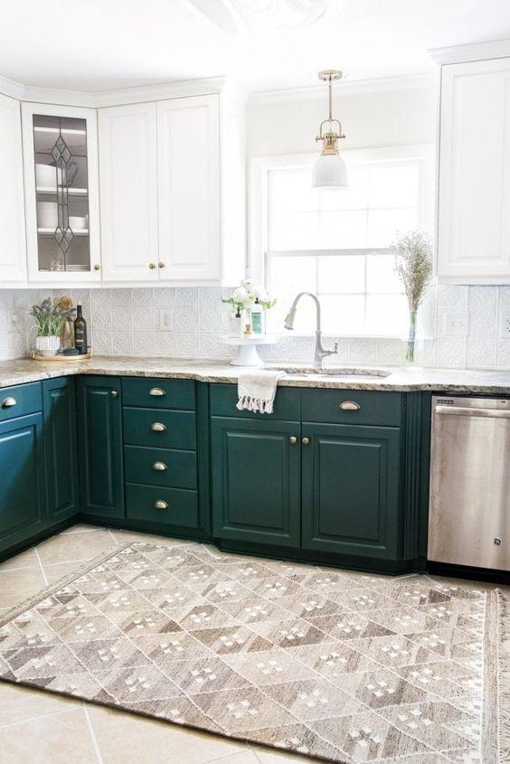 une cuisine élégante avec des armoires vert foncé et blanches, des comptoirs en pierre et des touches de métal ici et là