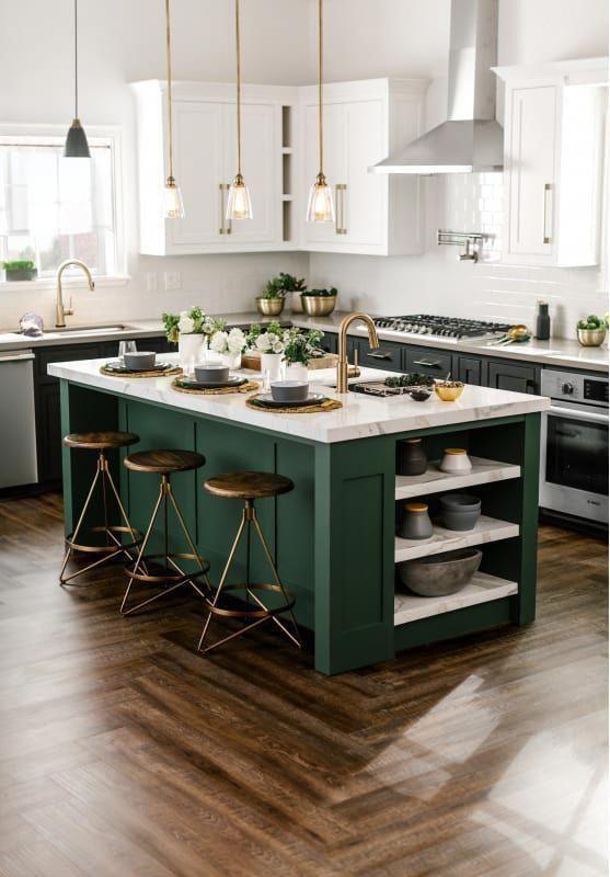 une élégante cuisine vert foncé et blanc avec des touches de laiton et des tabourets foncés ainsi que des comptoirs en marbre pour un look audacieux