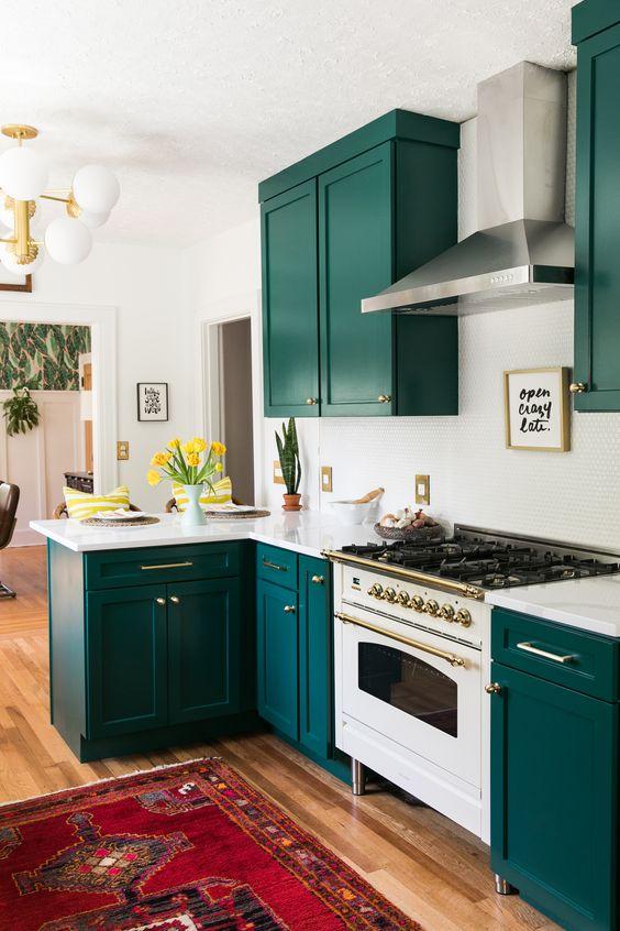 une cuisine super audacieuse avec des armoires sarcelles, un dosseret et des comptoirs en carreaux blancs et des touches dorées ici et là