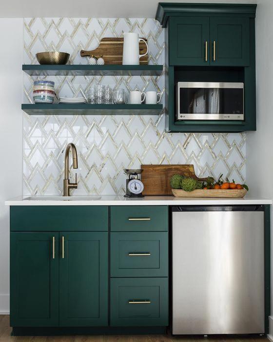 une cuisine élégante avec des armoires vert chasseur, un dosseret de carreaux en zig-zag et des touches d'or pour un look chic