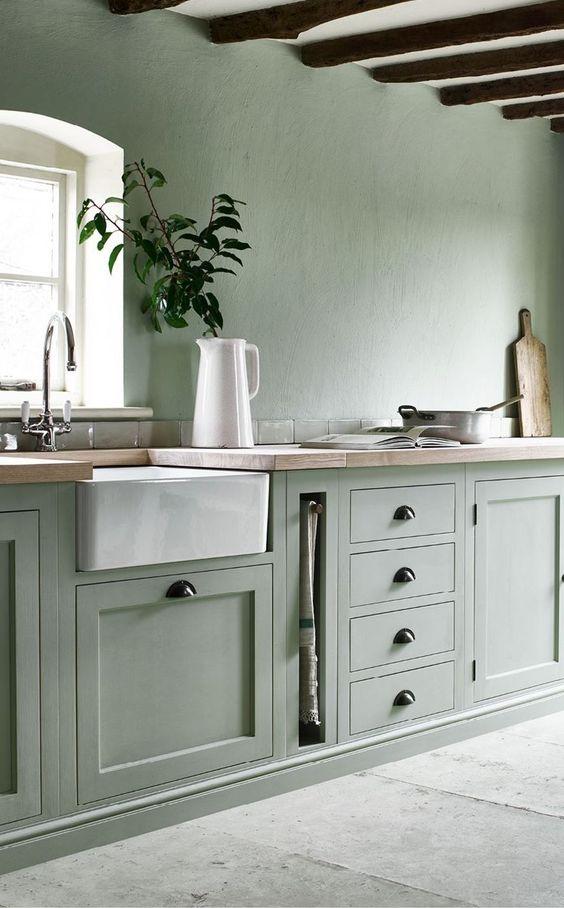 une cuisine vert pâle avec un plafond blanc et des appareils électroménagers ainsi que des poignées noires semble éthérée et très naturelle